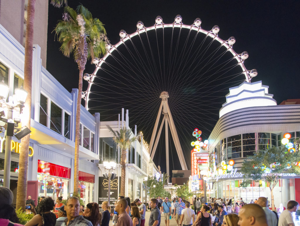 Las Vegas, Nevada, USA - June 7, 2014: People walking on the street next to retail shops and restaurants in front of the High Roller Ferris Wheel in Las Vegas during late night in the summer.