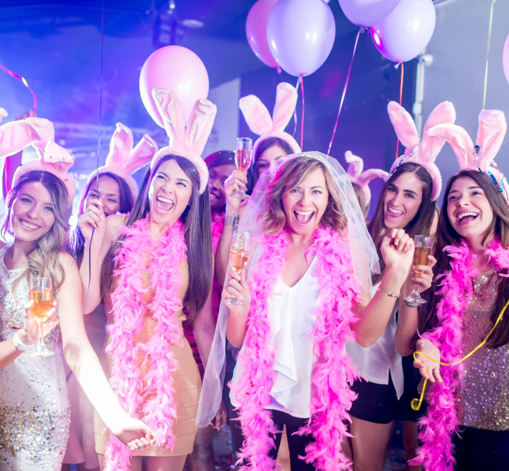 Bride wearing a veil having fun on her bachelorette party at a night club with a group of friends wearing bunny ears